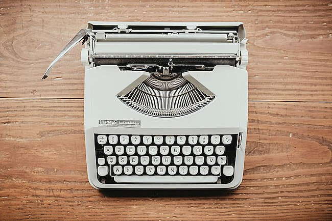 A mechanical typewriter. The lever for the carriage return is on the outer left side.
